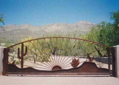Metal driveway gate with cactus, sun and coyote design